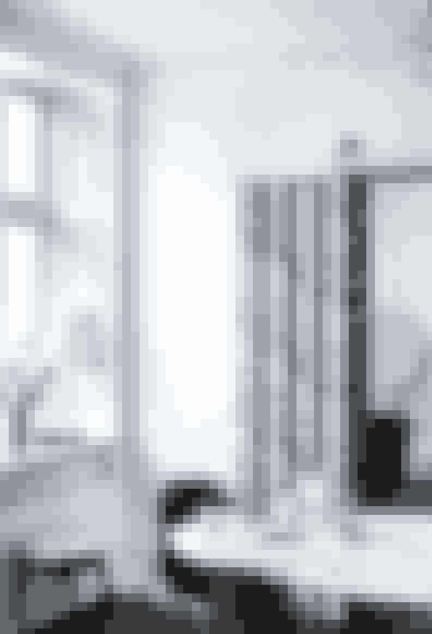 Da parret skulle renovere lejligheden, var det oplagt ikke alene at fylde den med kunst, men også at integrere et værk i selve rummene. Det blev et sæt moderne fløjdøre af kunstner-duoen Bank Rau, der skiller spisestuen fra soveværelset. Lampen i vindueskarmen er fra Holmegaard med en skærm af Le Klint.