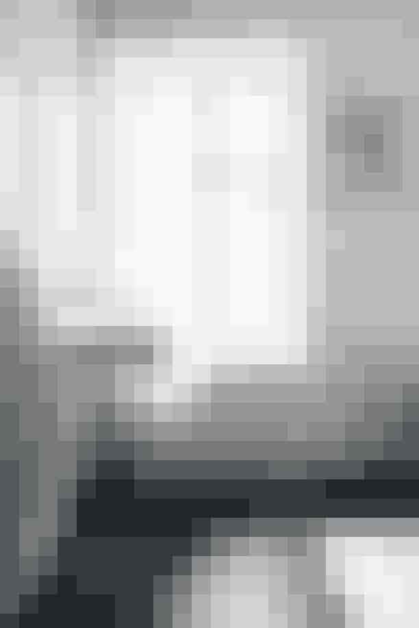 På gulvet i badeværelset ligger grønne mamorfliser, der er vednt med den glasfulde side nedad og derfor fremstår matte. Messingarmatuerne er fra Toni, og det sorte glasskab er købt antikvarisk. Papirklippet er fra Mette webshp Ohsofine.dk