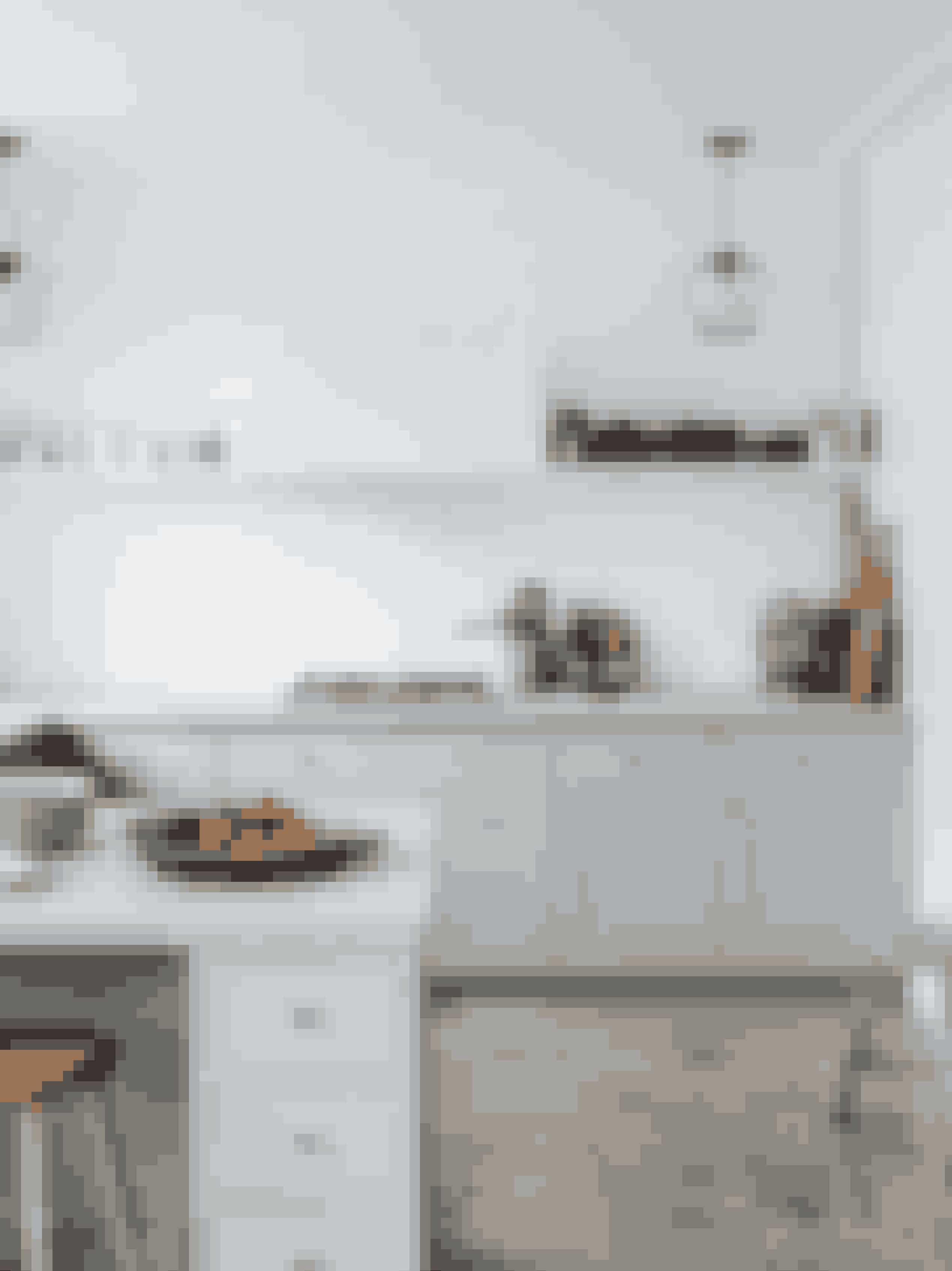 Køkkenet er lavet i samarbejde med møbelsnedker Albert Daubjerg. Porcelænet er fra Royal Copenhagen, de sorte skåle og tekanden er fra Kähler, og lamperne er fra &Tradition. Taburetterne er fundet hos henholdsvis Rosmosegaard og Trævarefabrikken. Marmorfadet til frugt og grønt er fra Studio Oliver Gustav.