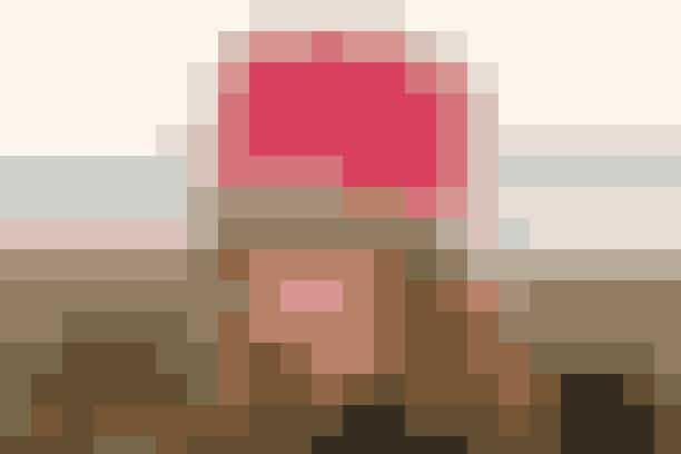"""Hatten med den høje puld er strikket med tre tråde alpakka i alle fire farver, toppen dog kun med to tråde garn  STRIKKET HAT Hovedvidde: 55-56 (58-59) cm, højde ca. 15 cm.  Materialer: """"Alpaca"""" (100% alpakka/50 g = 180 meter): 150 g rød nr. 3620 + 100 g pink nr. 2921 + 50 g sort nr. 8903 + 50 g råhvid nr. 0100. Strømpep + rundp (40 cm) nr. 3½. (Garn fra Garnstudio, tlf. 80 01 81 71). Strikkefasthed: 23 m x 30 p = 10 x 10 cm i glat med 2-3 tråde garn.   Hat: Slå 120 (126) m op på rundp med 3 tråde sort garn. Strik 4 omg glat, derefter mønster efter dia (brug 3 tråde i hver farve). Når dia er strikket færdig: Forts med 3 tråde rød og strik 4 omg glat. Bryd så den ene tråd, strik videre med kun 2 tråde rød og tag 8 (6) m ind (strik 2 r sm) jævnt fordelt på 1. omg = 112 (120) m. Sæt 8 mrk i arb med 14 (15) m's mellemrum. Skift til strømpep undervejs, og tag nu 1 m ind efter alle mrk på hver 3. omg 4 (6) gange, derefter på hver 2. omg 5 (5) gange og på hver omg 4 (2) gange = 8 (16) m tilb på omg. Næste omg: Strik alle m sm 2 og 2, bryd trådene og før enderne igennem rest 4 (8) m. Træk sm og hæft.    Strikkeopskrift: Drops"""
