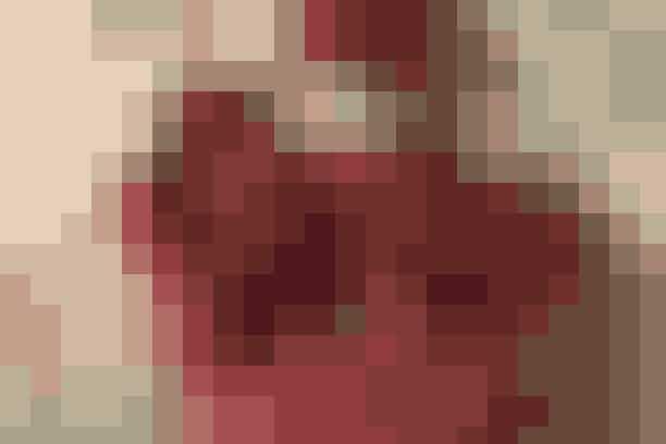 """Nissen i den fine hjertepose vogter over de små kalendergaver      NISSE   Højde: 28 cm.  Materialer: 25 x 40 cm stribet stof. 6 x 20 cm hudfarvet stof. 10 x 40 cm mørkerødt stof. 3 små knapper. Polyesterfyld. 3 x 30 cm orange fleece (halstørklæde). 1 bjælde. Brodergarn.  Alle mønstre : Kan hentes ved at klikke her  Se forkortelser og brugertips her  Arbejdsgang: Skær stofstykkerne efter de opgivne mål på skitse A og B. Sy strimlerne sammen med 1 cm's sømrum. Pres alle sømrum opad mod huen. Forstør nissemønstret 200% i kopimaskine og overfør det til karton. Tegn mønstret op på vrangen af del A, og klip modellen ud 1 cm uden for denne streg. Broder øjne, næse og mund på, og sy knapperne fast. Læg denne del ret mod ret med del B og sy rundt i stregen, men lad 6 cm stå åben i den ene side. Klip sømrummet ned til 4 mm, og hak sømrummet i rundingerne. Vend retten ud og put fyld i. Sy åbningen til. Sy gennem alle lag ved hals, markering af ærmer og ved benene. Sy bjælde i hatten. Klip 3 cm frynser i begge ender af halstørklædet, bind og hæft halstørklædet fast.    HJERTE  Højde: 22 cm.  Materialer: 2 stk. prikket fleece a 25 x 25 cm. 2 stk. rødt bomuld a 25 x 25 cm. 80 cm rødt skråbånd.  Arbejdsgang: Forstør hjertemønstret 200% i kopimaskine og overfør det til karton. Klip 2 hjerter i fleece med 1 cm's sømrum. Hæft det røde bomuld ret mod ret med fleecen og sy delene sm rundt foroven i buerne fra pil til pil, klip bomulden til. Klip et hak ved hvert mærke i begge sider og klip den nederste spids af det røde bomuld efter fleecen. Hæft delene oven på hinanden vrang mod vrang, og sy """"bunden"""" af de 2 dele sm. Klip sømrummet ned til 4 mm og sy skråbånd på (start nederst i spidsen), så det dækker sammensyningen, samtidig med at båndet sys sm mellem buerne.    Syopskrift: Ruth Møller/Foto: Jette M. Vesterager"""