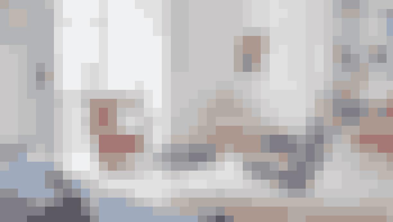 Den store, lyse stue er minimalistisk indrettet med få pynteting, så de klassiske møbler rigtig kommer til deres ret. Sofaen er en arkitekttegnet sag fra 50'erne, købt på Lauritz.com, sofabord fra Eames, lænestol fra Lauritz.com, Poul Kjærholm-læderstol, lampen er af Arne Jacobsen, og i hjørnet står en lænestol fra Bertoia. Billedet til venstre er af Grace Coobens og det til højre af Emil Madsen Brandt.