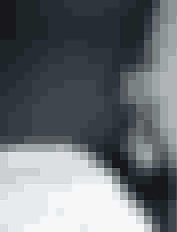 Skråvægge bidrager med en god portion charme, her i soveværelset. Den gennemsigtige plastlampe er fra Kartell. Sengebordet i mørkt træ er købt brugt.TIP:Mal en enkelt væg i en anden farve for at skabe kontrast. Her fremhæver den mørke væg det hvide og lysegrå sengetøj.
