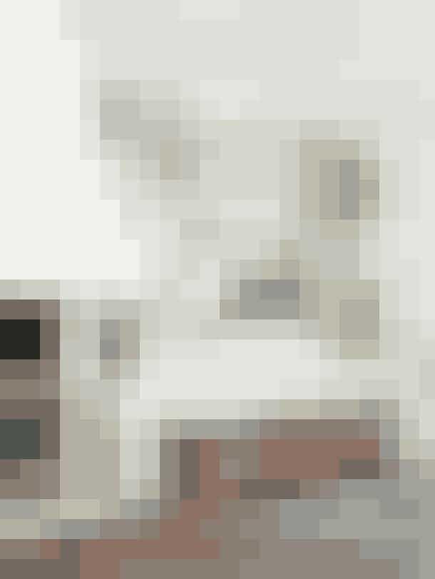 Udnyt hele væggens højde, når du lave en billedvæg, og få en uformel salonophængning, som man ser det på caféer i Paris.Billedvæggen i stuen er sammensat af et mix af fotografier, litografier, tegninger og malerier. Bænken er et loppefund, som parret selv har malet i en fin lyserød farve.