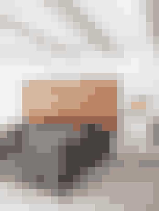 En stor blød cognacfarvet sengegavl i læder giver varm og hyggelig stemning i det enkle soveværelse sammen med en lang etnisk udseende pude og en stofpendel fra Venedig. Gavlen er fra en vintagebutik, sengetæppet har Karen Simonsen selv designet, det transparente glasbord er fra Klassik, og lampen med den stribede skærm er fra Io Scandinavia.