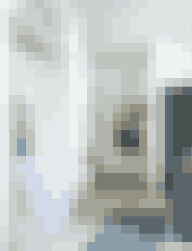 Den åbne entré leder direkte ind i køkken-alrummet. Bag køkkenet er der et lille rum, der fungerer som walk-in-closet til jakker og sko. Konsolbordet er fra Magnifique, pendlen er fra butikken Dansk på Vesterbro i København, og det store abstrakte maleri er et af Cecilie Hertzs egne værker.
