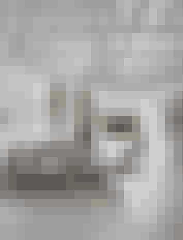 Anette har kombineret en moderne sofa med møbler i naturmaterialer for at give stoflighed og hygge til husets rene linjer. Sofaen er fra Ilva, gulvtæppet fra Ikea, lampen og træsofabordet er hjemmelavet, mens kurvestolen er et loppefund. Plakaten er fra Køges Skitsesamling, og maleriet har Anette har selv malet.