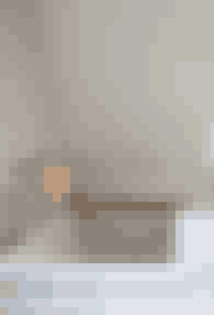 Badeværelset er et studie i rene linjer; hvid sanitet, varme detaljer i træ og stearinlys, så man får lyst til at blive liggende i badekarret lidt længere.  Tekst og foto: Iben og Niels Ahlberg