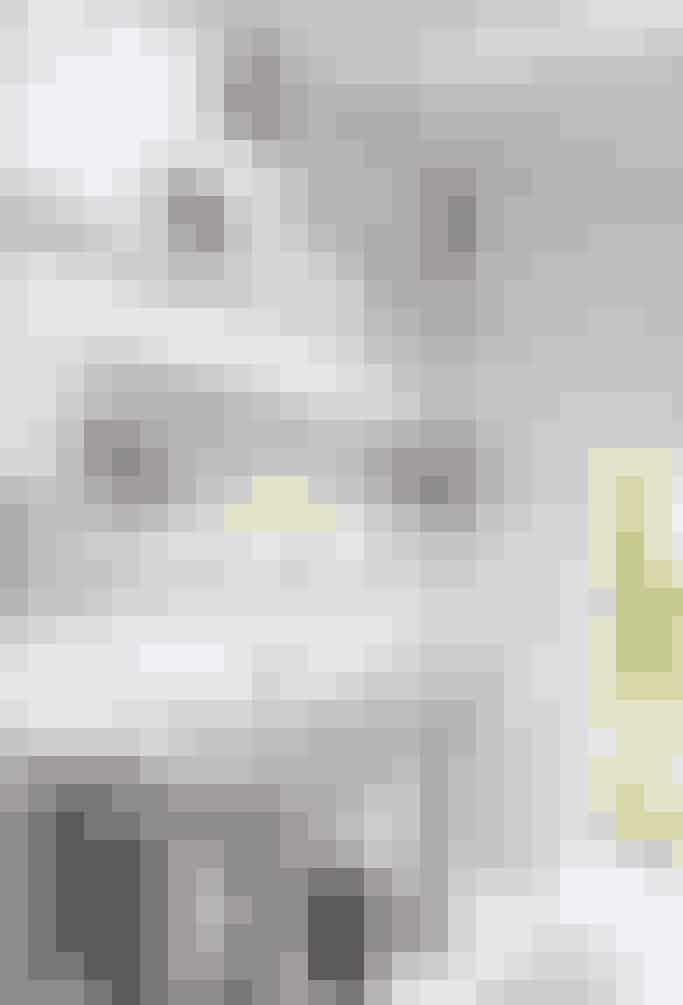 Fin, hvid sanitet i den gamle franske stil, en enkel buket af blomster fra haven og smukke gamle rammer på hylden over vaskene giver et romantisk badeværelser i flot fransk stil.  Af Tatjana Quax / Foto: Ben Lambers/Studio Aandacht
