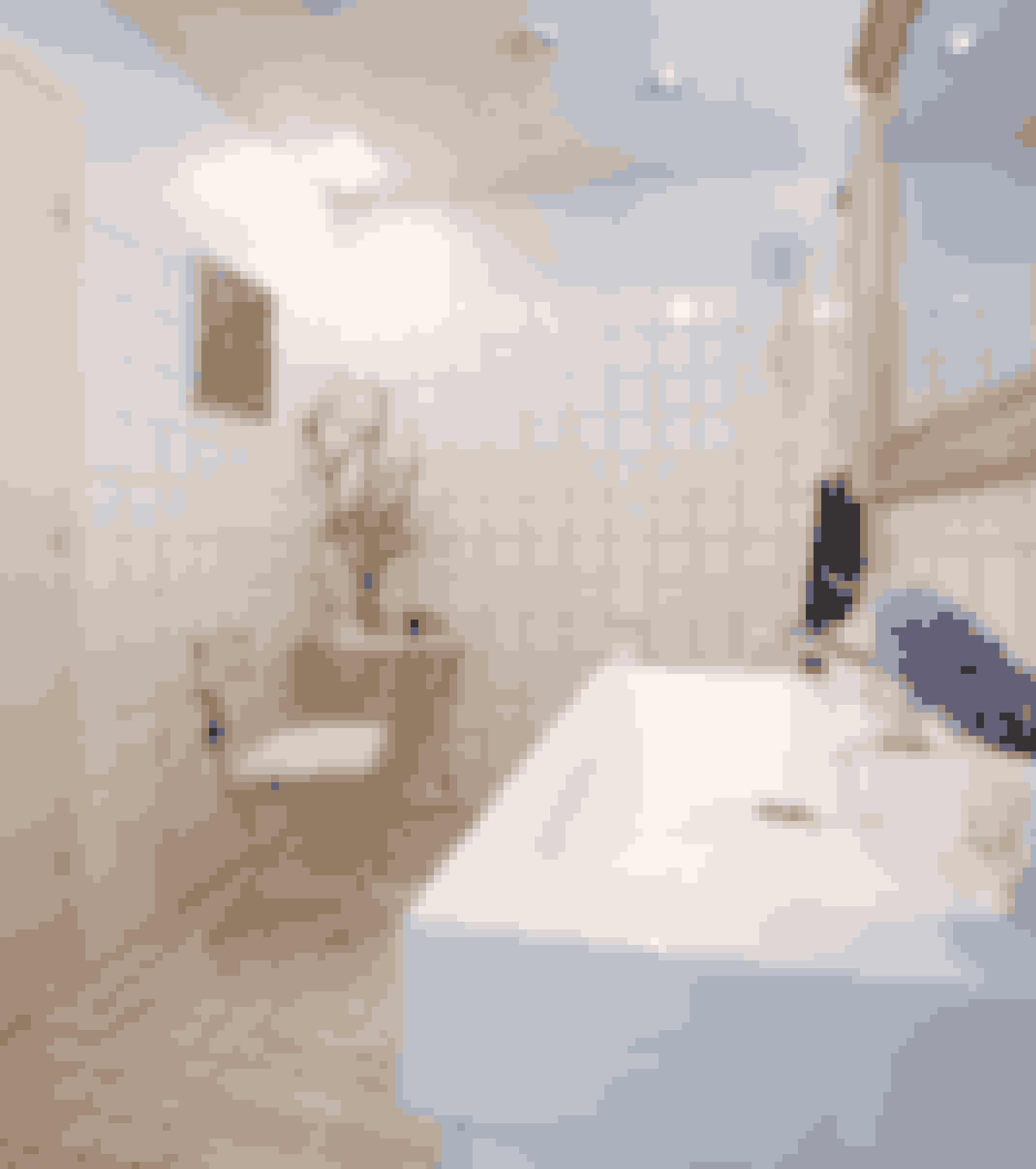 Der skal ikke så meget til for at pifte et almindeligt badeværelse med hvide klinker op. Er der ikke plads til et lille cafébord, kan blomster og billeder også gøre meget.  Foto: Lene Karin Kristiansen
