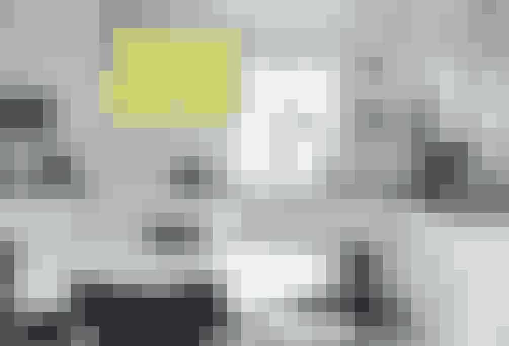 Både køkkenet og spisepladsen er holdt helt enkelt i sort og hvidt. Dog brudt af den store gule pendel over spisebordet, der overrasker og bløder rummet op.  Af Katrine Martensen-Larsen / Foto: Mikkel Adsbøl
