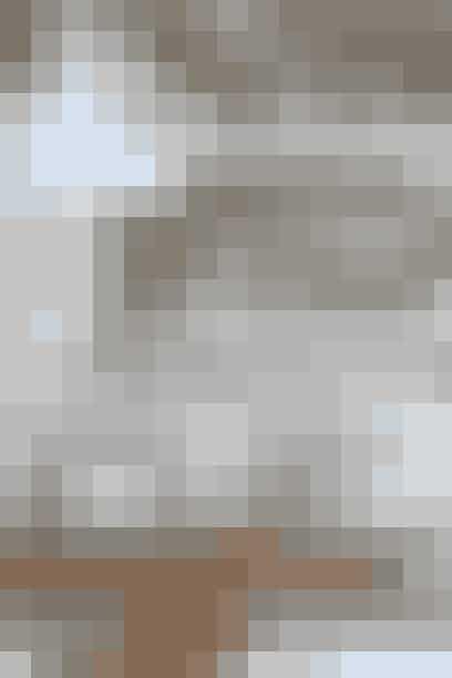 Industrikøkkenet er af mærket Boform og matcher murstensvæggen. Kombiner det med lamper og tilbehør i en sart lyseblå nuance. Det bløder det rå industrilook op. Du kan bryde en rå væg med en hylde i en farve, der råber op. Her er det en hvid blank hylde mod den rå køkkenvæg. Server også salt og peber i skaller som her.