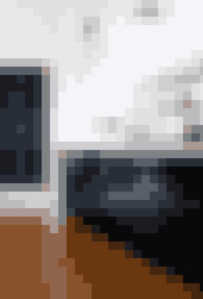 Køkkenelementer og reolen er malet med sort højglansmaling som industrielt modspil til de hvide vægge og den elegante sildebensparket. Og så har de indbyggede skabe på bagvæggen også fået en omgang sort maling. En rigtig nem måde at få køkkenet til at hænge sammen på, selv om skabslågerne er vidt forskellige.