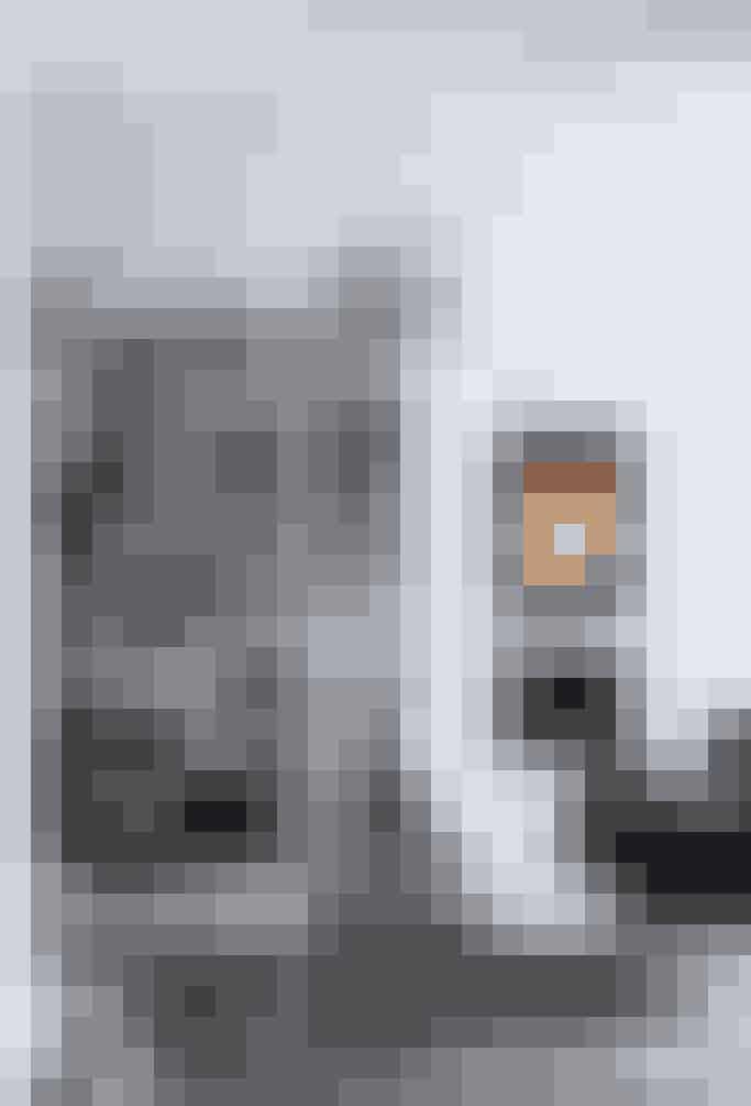 Brændeovnen danner et grafisk udtryk op imod Arne Jacobsens rundede Svanestole og -sofa, fundet på Lauritz. com, og den grafiske reol Random fra MDF Italia. Bordet er en af favoritterne fra Bloomingville i kinesisk genbrugselmetræ. PH\'s kogle og tæppet Posh Fashionation fra Haus samler møblementet i midten af rummet med udsigt til pejsen til den ene side og køkkenet til den anden.