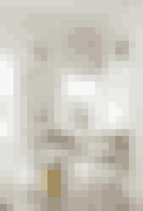 Der er god plads til en hyggelig spisekrog i køkkenet, som er holdt i neutrale farver tilsat enkle markante gule elementer. Camilla Bernal har valgt en specialbygget bænk til hjørnet, som bruges til opbevaring. Bænken har hun fyldt med masser af puder, tilsvarende puder kan blandt andet fås hos Lene Bjerre. Den gule taburet er fra Quirky.Me.