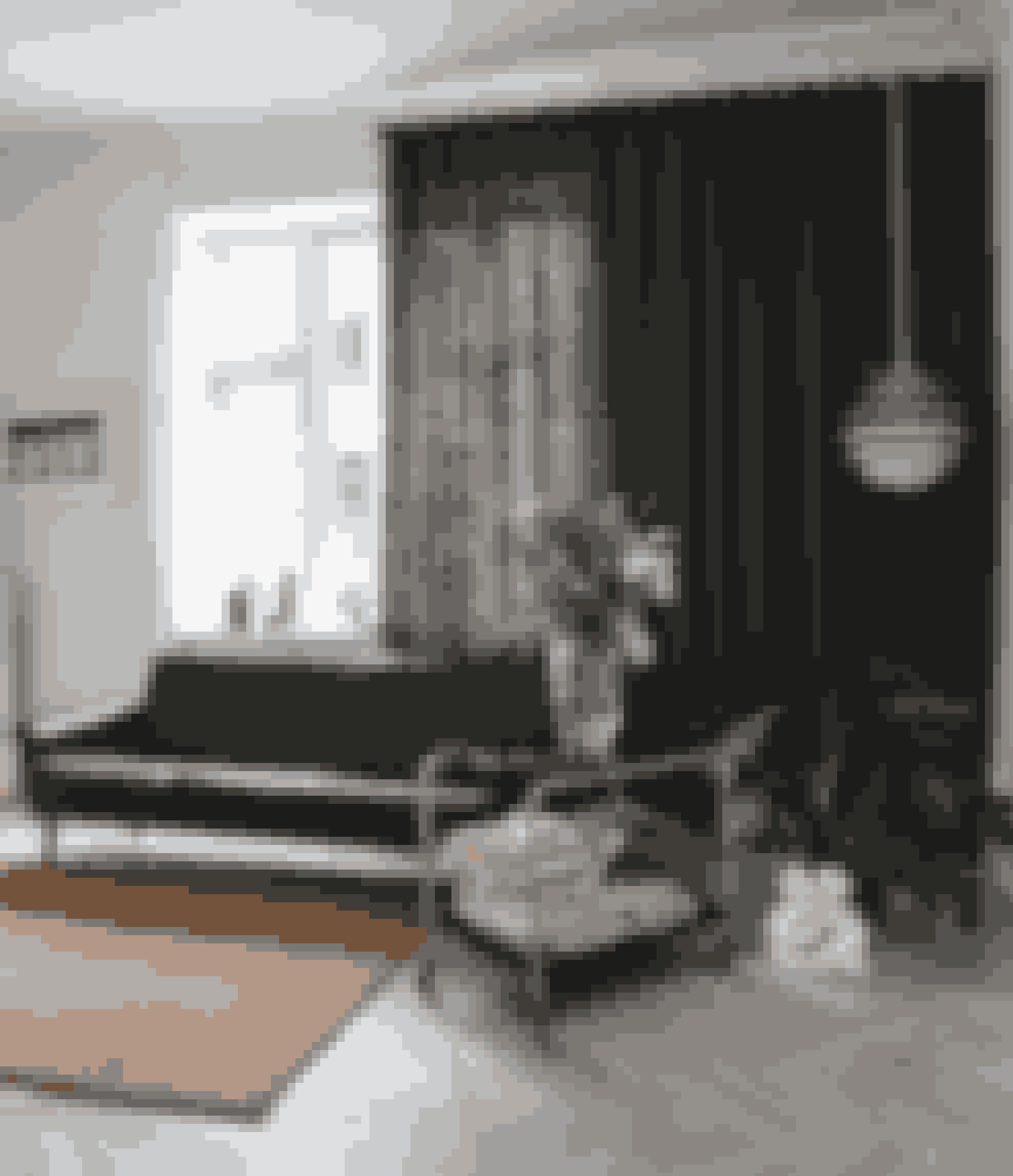 Hæng gulvlange gardiner op på den ene side af vinduet, og lad gardinstangen gå helt ind til væggen. Det giver en rolig flade. Samtidig forbedrer tekstiler lyden i højloftede rum. Sille har selv syet gardinet af olivengrønt hør. Sofaen har tilhørt Silles bedsteforældre, den gamle PH-lampe tilhører en af Silles venner, og gulvtæppet er fra Hay. Skulpturen er en gipsafstøbning fra Rudolph Tegners Museum & Statuepark.