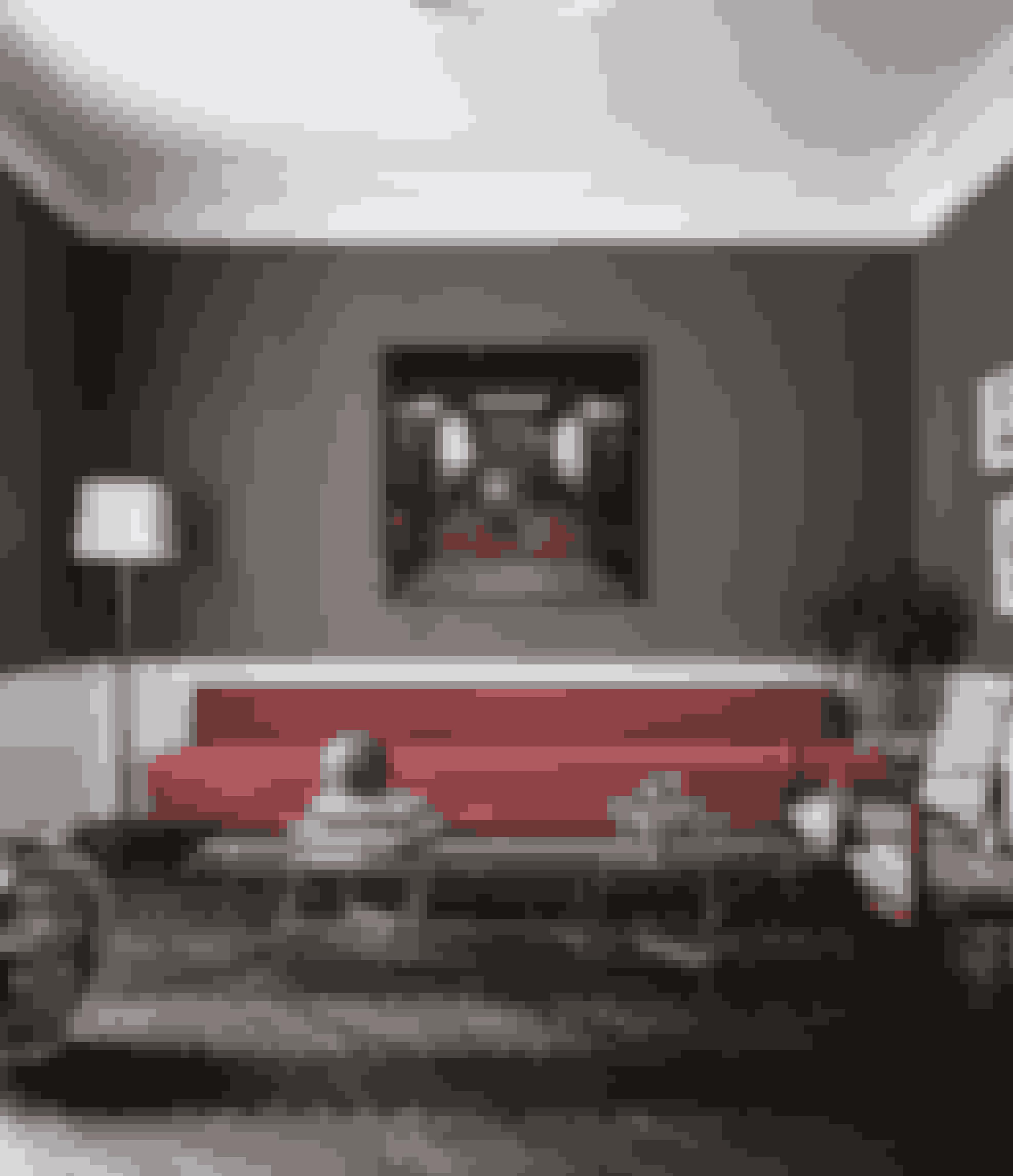 Mørke vægge giver en kontrastfuld ramme og fremhæver panelerne. Ved at vælge en meget lang sofa understreger du den klassiske indretning. Den tre meter lange sofa Modern Line er af Gretha Grossman hos Gubi. Maleriet er af Niels Corfitzen fra Galleri Oxholm, glasbord er fra Gallotti & Radice, Kaare Klints safaristole er købt på en auktion, og de fleksible lysestager er Nagel-stager.