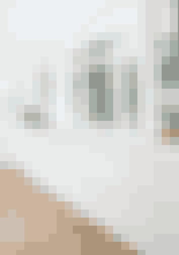 Det enkle look er skabt ved at vælge hvide, minimalistiske køkkenelementer, der smyger sig lige ind i de højtloftede og hvide rum.