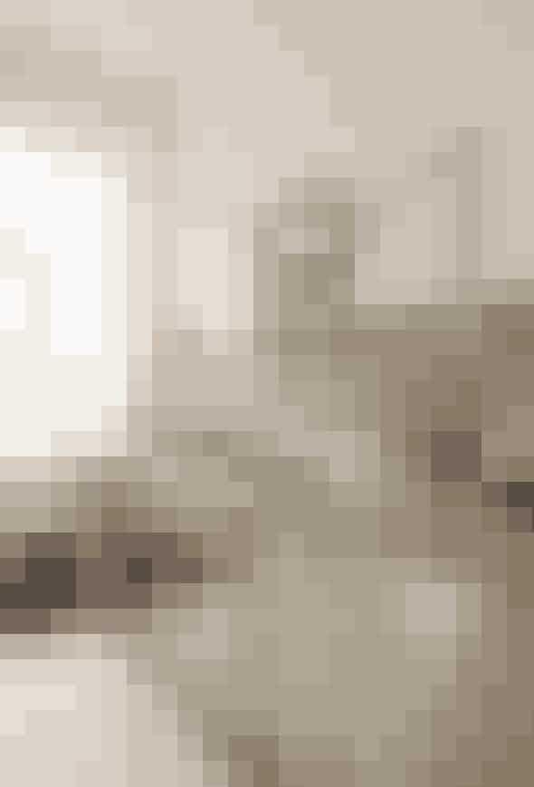 Gør en dyd ud af at vise din godt slidte træbordplade frem. Giv den nogle flere skrammer og mærker, og lad den tale sit eget rustikke sprog dækket af en tyk glasplade. Mal et bredt stykke fra væg til væg med afvaskelig maling i en støvet farve for at skabe kontrast til alt det hvide. Og som prikken over i'et kan to læselamper give det helt rigtige elegante og rå udtryk. Lamperne fra Artemide er fra Illums Bolighus. Stålkanden fra Georg Jensen, og den hvide kande fra Royal Copenhagen. Den gamle dåse er et loppefund.