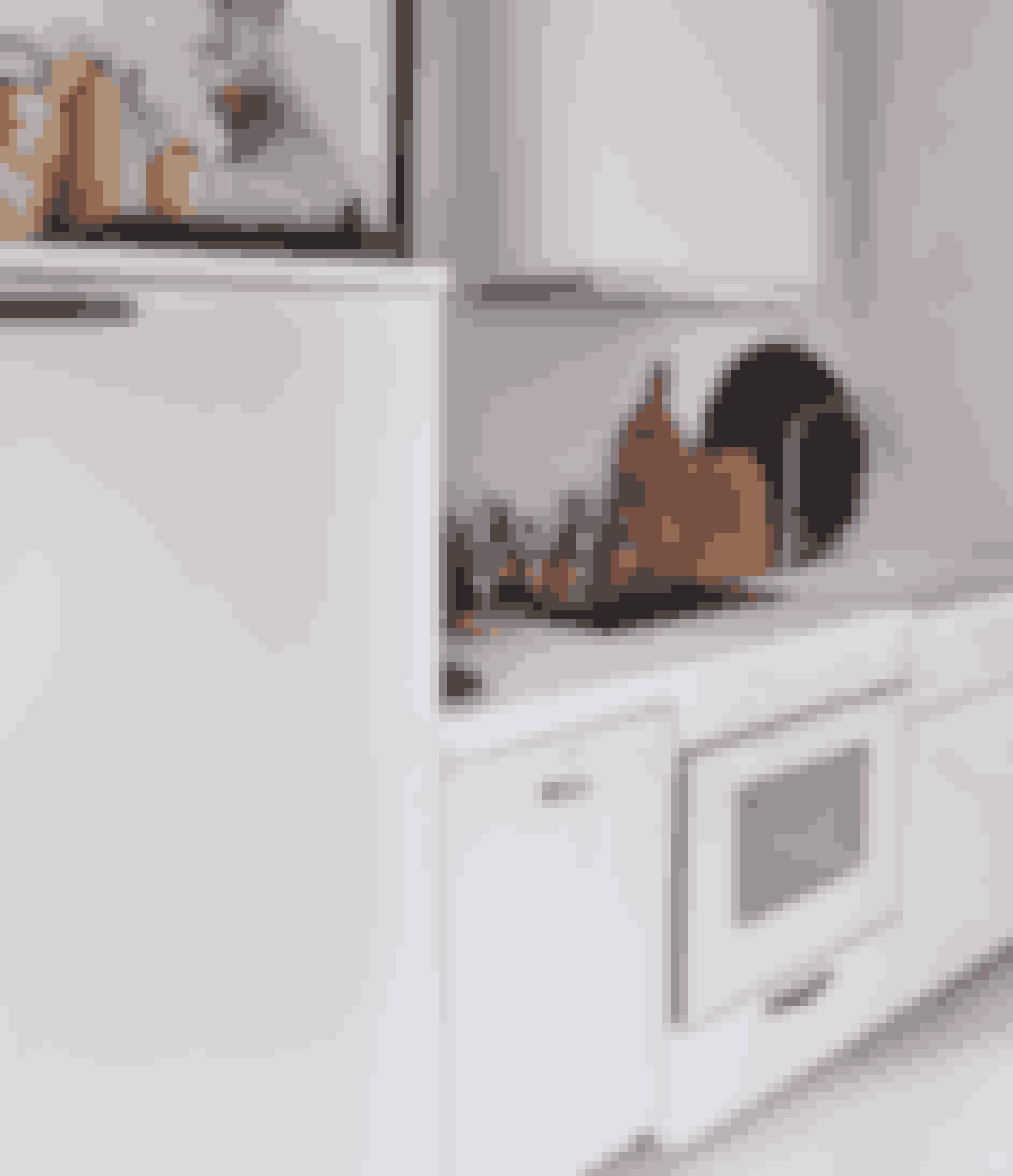 Gå efter bordplade, låger, emhætte og som her ovn i samme farve for at holde et roligt udtryk, selvom køkkenet er lille.