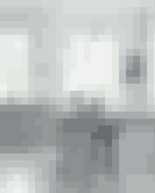 I stedet for store, grebsfrie køkkenlåger kan du gå efter masser af mindre skuffer med profil, hvis du ønsker et landligt køkken. Gråt gør det mindre klinisk end den klassiske hvide. Køkkenet er bygget af Handcrafted Interior, og vandhanen er fra Quooker. Pendlerne over bordet er modellen Anoli fra Nuura, og skamlen er fra By Lassen.