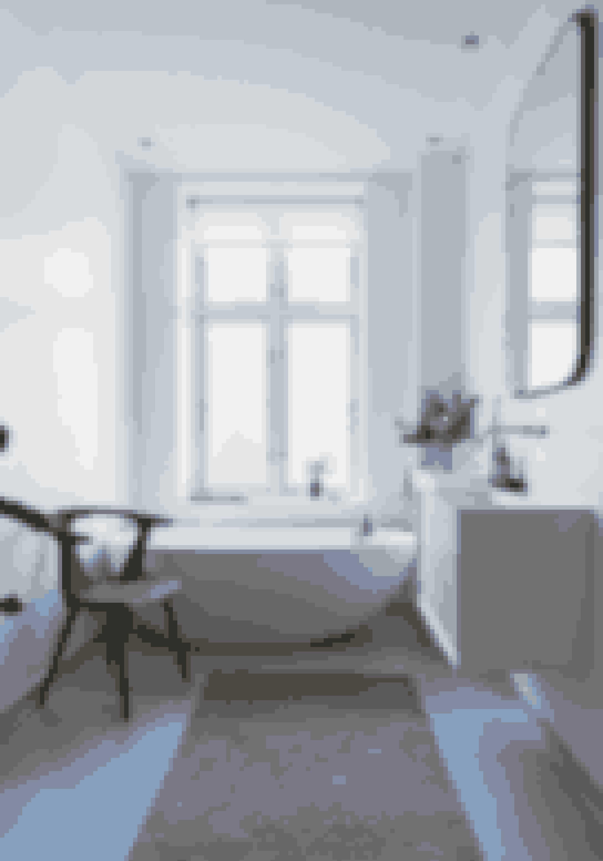 Prioritér et stort badekar, hvis du ønsker spafornemmelse. Brug tæpper og rigtige møbler til at bløde rummet op. Kar og vaskearrangement er fra Copenhagen Bath, armatur fra Vola, spejl fra Snowdrops Copenhagen, tæppe fra Magasin og stol i røget eg fra &tradition.