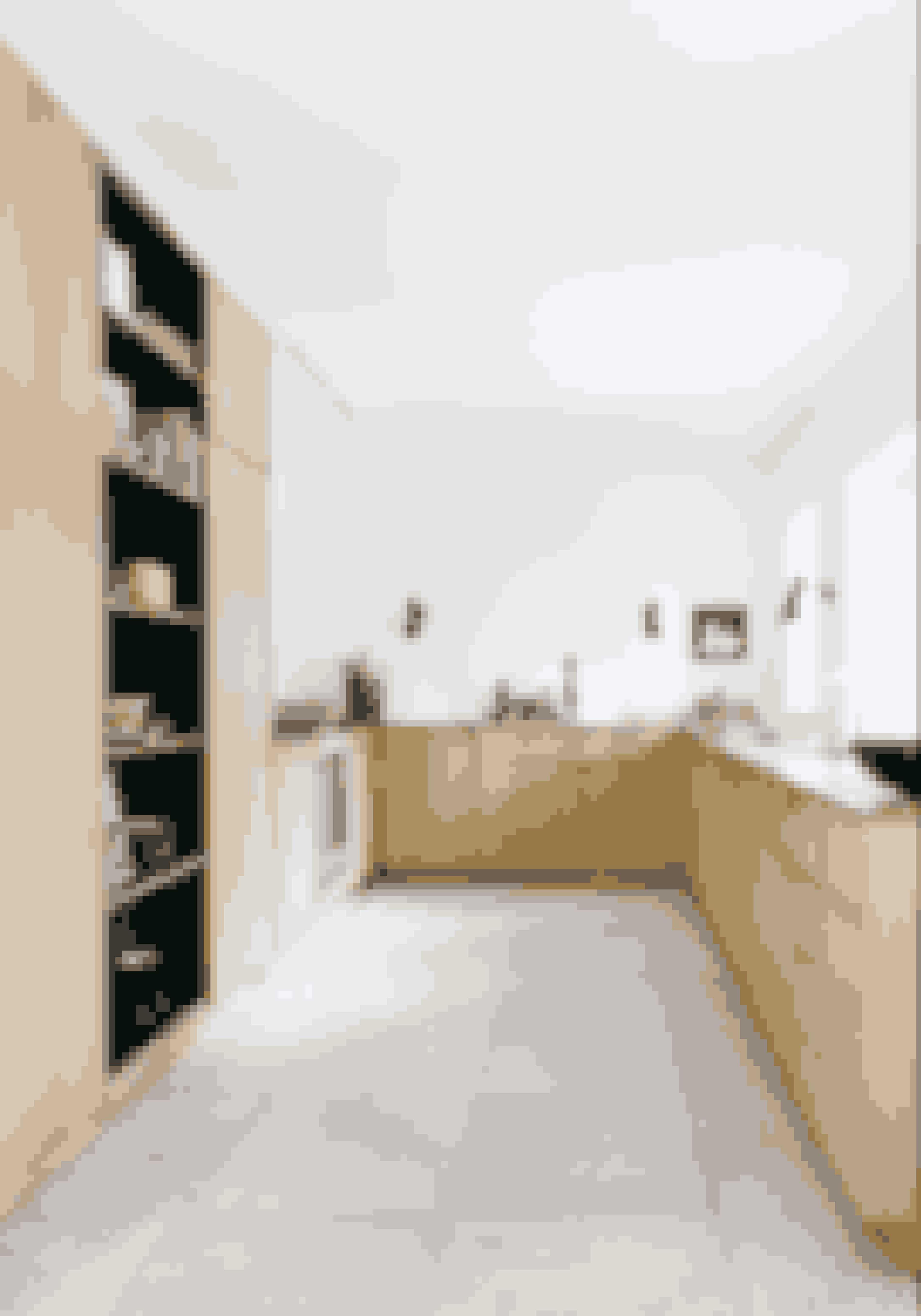 Vælg et køkken i materialer og stil, der passer til huset og den tid, det blev bygget i. Snedkerkøkken i massivt egetræ er fra Nicolaj Bo. De sorte AJ væglamper designet af Arne Jacobsen er fra Louis Poulsen. De Italienske fliser med tegnede fossiler fås hos Banio.