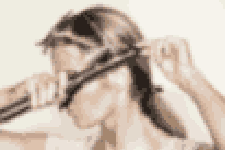 """Trin 2.Del dit hår op i to sektioner. Tag en lok hår over øret fra den mindre sektion og rul det omkring krøllejernet""""ghd curve® soft curl tong"""". Hold den i en vandret position og vent 3-5 sekunder og slip håret"""