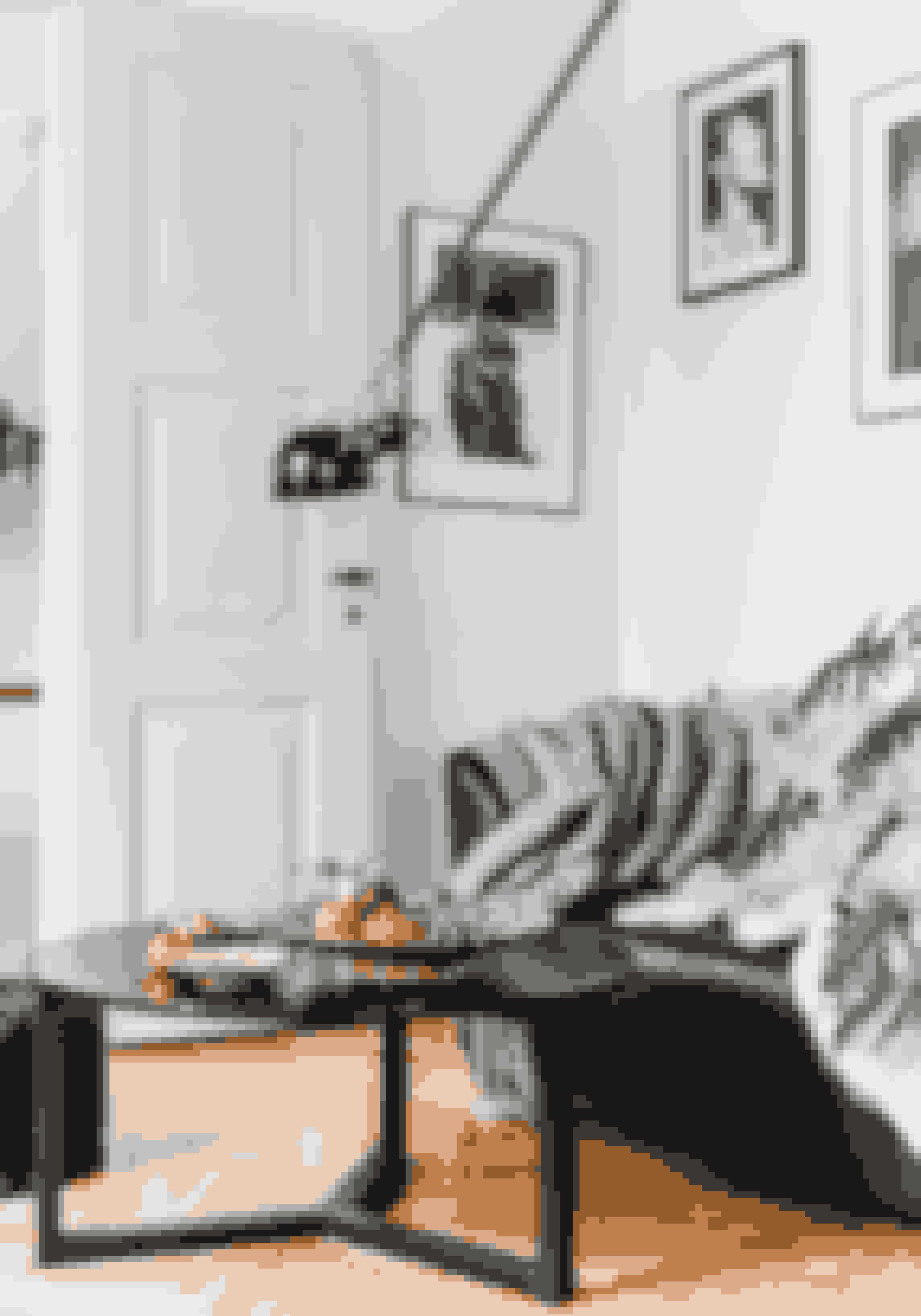 Blød en monokrom farveskala op med pynt i form af klementiner. Den sorte svingarmslampe er fra Flos.