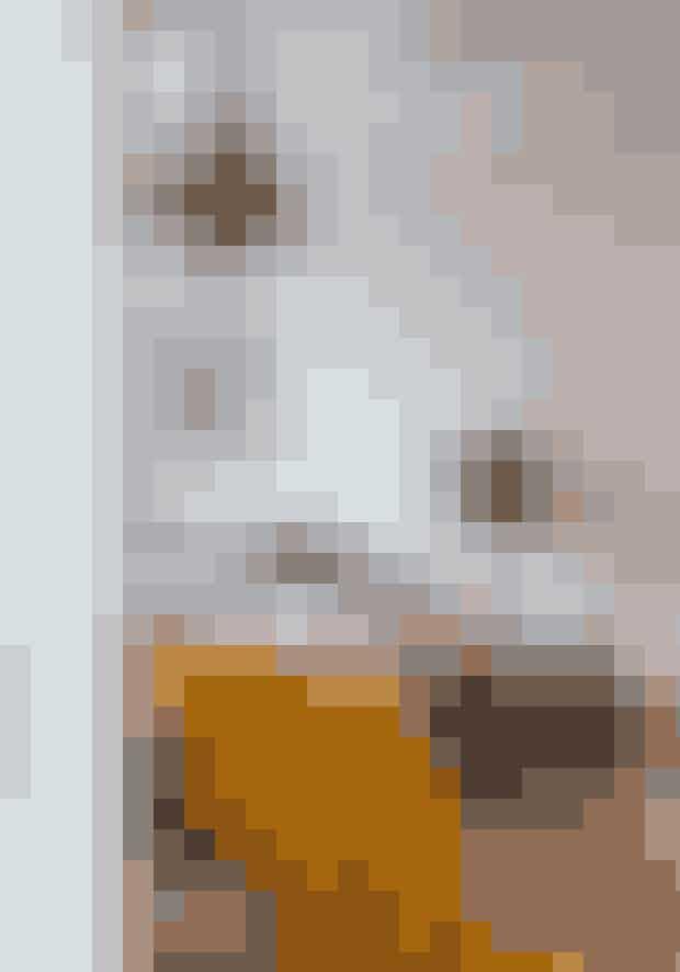 Med en stor buket mistelten i de franske døre mellem to rum får du fuldt blus på julestemningen med få midler. Det antikke sengebord er købt hos Rosmosegård, lampen er fra Design by Us, puderne og det gule tæppe er fra Gubi, og det grå sengetøj fra Fabric Copenhagen.