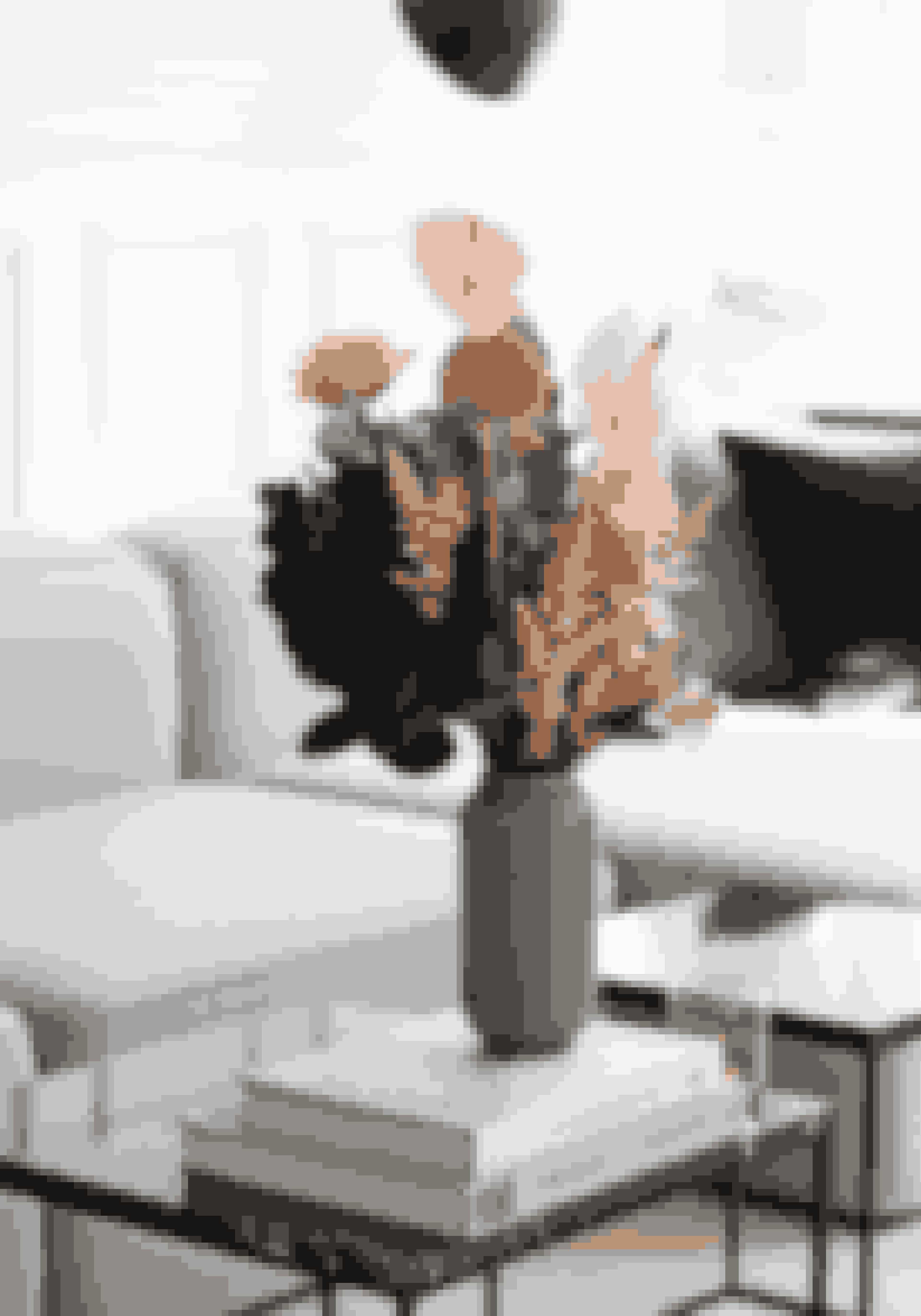 Skab farve i hjemmet med friske blomster, og brug buketterne i stedet for tilbehør eller som her i et helt enkelt stilleben sammen med bøger. Buketten er fra Poppy Kalas og bordet fra IDEmøbler.