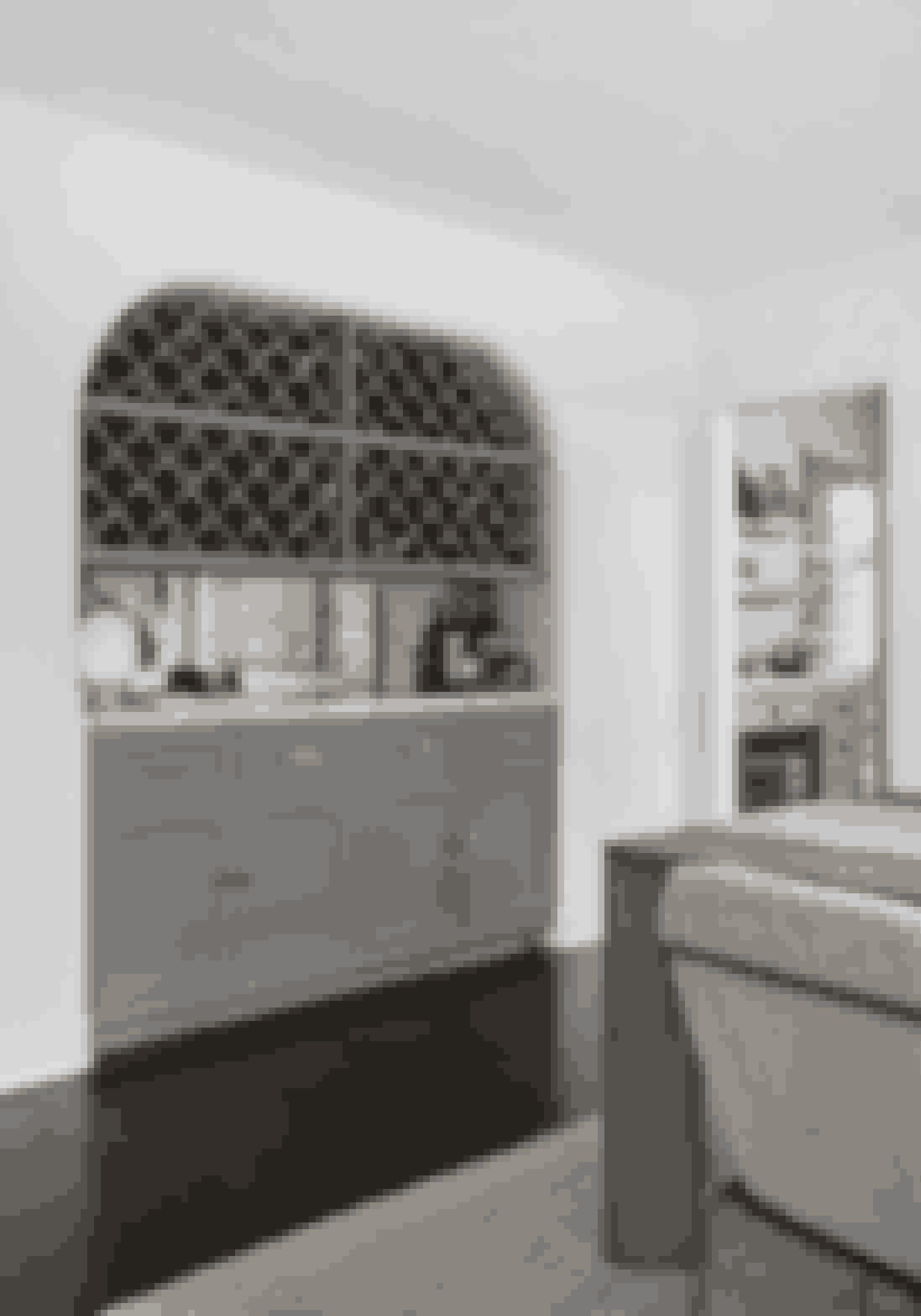 Integrér en vinreol i indretningen. Du kan fx lave en halvvæg mellem to rum, eller som her bruge buen i døråbningen til både vinreol, skab og hjemmebar.