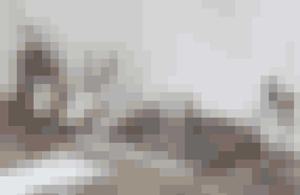 Det antikke skrivebord i stuen har masser af patina og personlighed. På en af bøgerne ligger en antik notesbog fra Beau Marché, foran notehæfter fra Hay, og Kubus-lysestagen er fra Paustian. Prøv at tænke ud af boksen, når du indretter, som her,hvor en vase fra Ditte Fischer er blevet hjem for pensler.