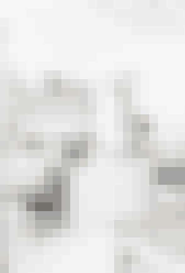 Åbne hylder og masser af lamper i forskellige niveauer forvandler det hvide køkken fra klinisk til imødekommende. Kombineret med et mix af designklassikerne, en Harry Bertoia- og en Panton-stol og et slidt spisebord, som Shelley Street har betalt sølle 45 kr. for på et loppemarked, bliver køkkenet hyggeligt. De høje stålindrammede glasdøre leder ud til en lille gårdplads.