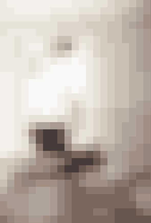 En hyggekrog i ægte herrestil og en retrohyldest med de brune nuancer. Et lignende tapet kan findes hos Retro Villa, og både Eameslænestolen i læder, gulvlampen med marmorfod og de tre små sideborde er vintagefund.