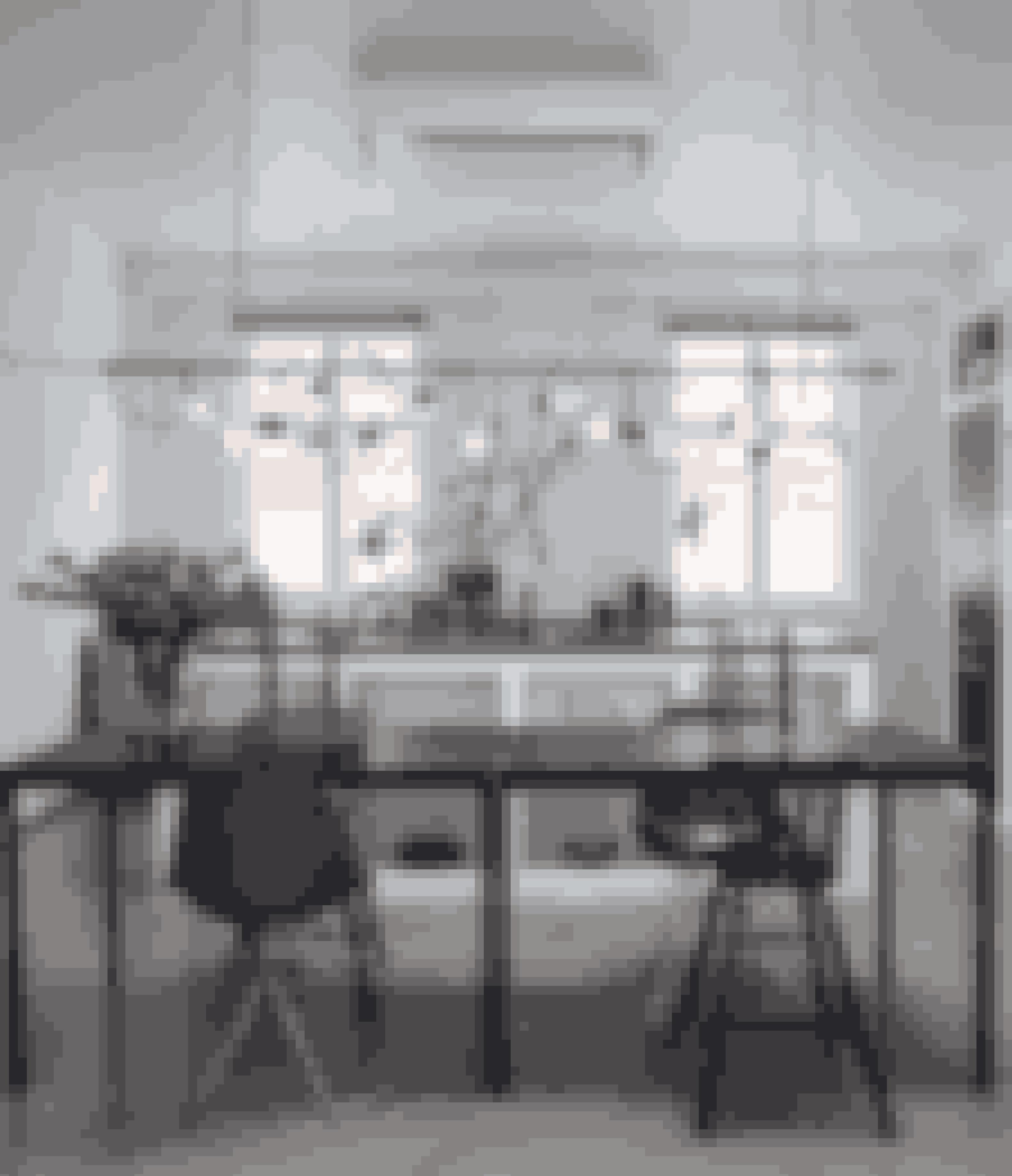 Få og store stjerner i rå naturlige materialer er sammen med kogler hængt op i den gardinstang, der til hverdag fungerer som lys over spisebordet. Familien har ikke fundet det helt rigtige spisebord endnu, så foreløbig bruger de to lette borde fra Ikea. De passer godt til det åbne køkkens hvide gasbetonelementer, stålskabet fra Fil de Fer, det grå betongulv og de sorte Eames-stole.