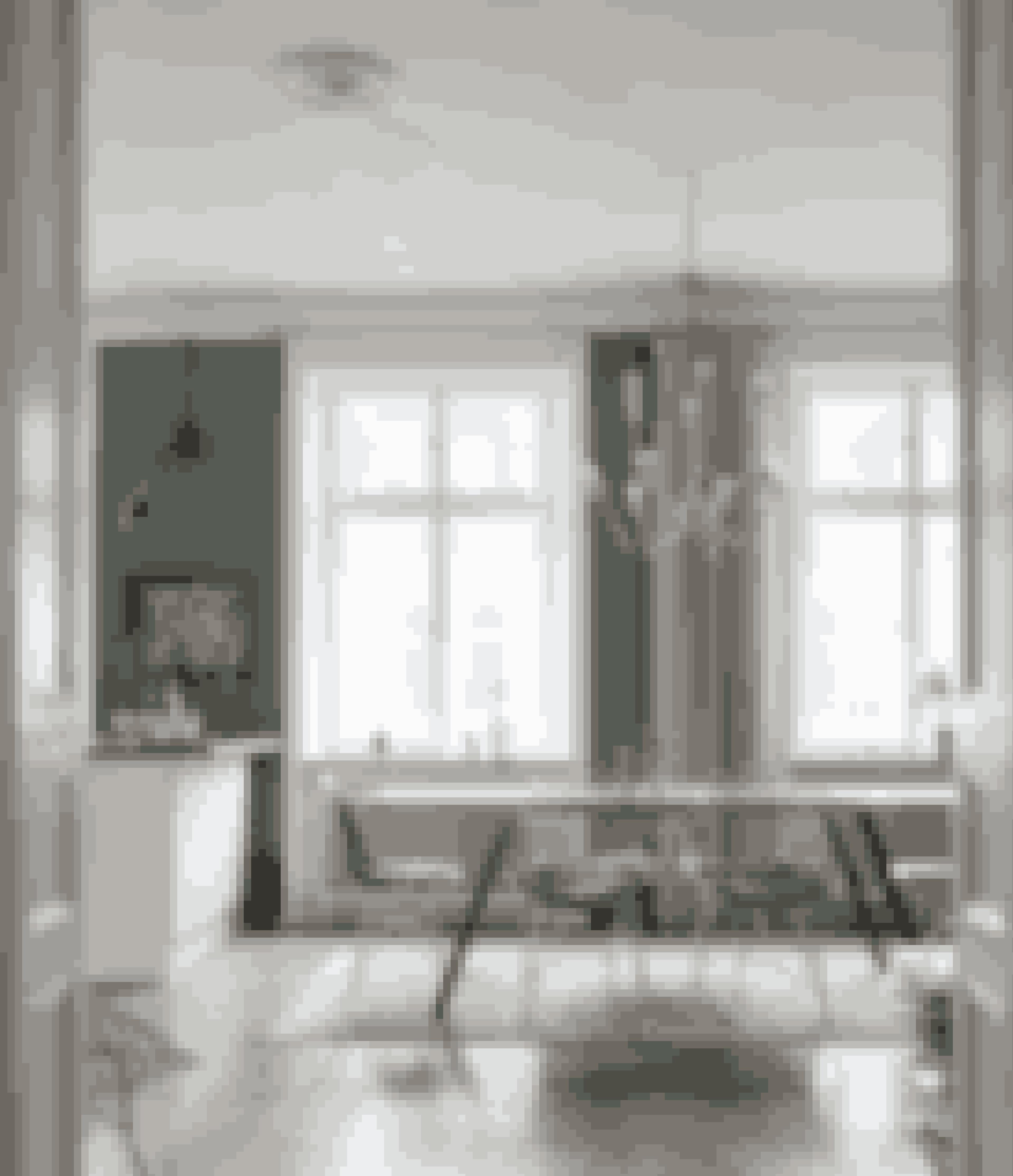 Ved at sætte spisebordet på langs i forlængelse af køkkenet, kommer der masser af luft i stuen, og det er nemt at bevæge sig rundt mellem rummene. Spisebordsstolene er af Eames og Harry Bertoia, spisebordet er lavet af gamle tagplanker fra Frankrig med et svejset understel, og lysekronen er fra Autoban i Istanbul.