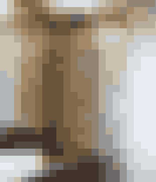 Hvis badeværelset skal fremstå som et eksklusivt hotelværelse, så er en genvej at bruge varme metaller. Her i form af en gylden mosaikvæg fra Bad & Fliser. Underskabene er af sortmalet træ fra HTH, armaturet fra Grohe, vasken fra Ikea og sæbedispenseren fra Vipp.
