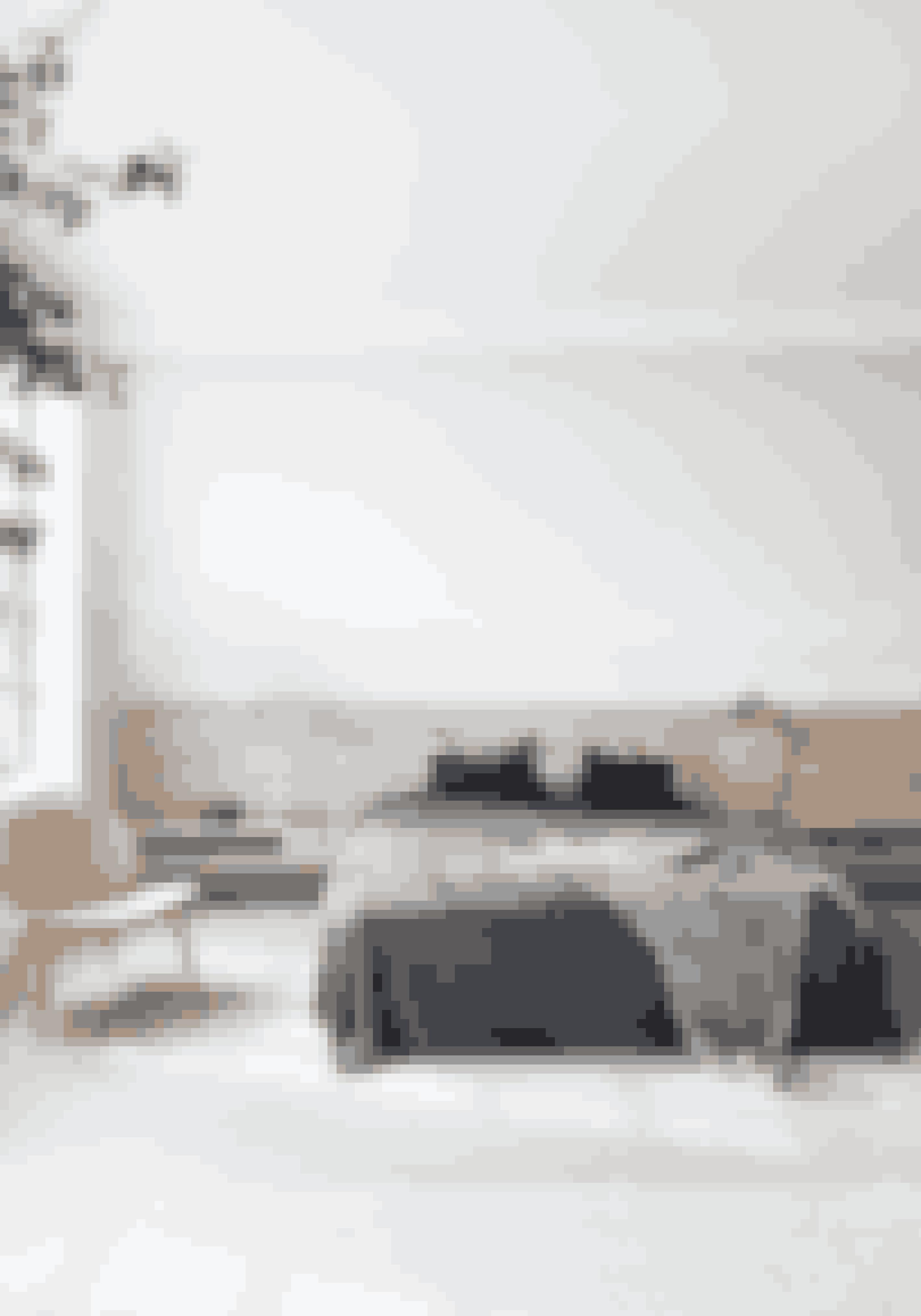 Vælg samme, afdæmpede farver som i lejlighedens øvrige rum i soveværelset, og brug træ som sengegavl for at opnå et let, lyst og nordisk i udtryk. Invitér en smule af naturen indenfor i form af store gulvplanter. Sengegavlen med indbyggede sengeborde er lavet af Dinesen Gulve. Både sengetæppe og plaid er fra Aiayu.