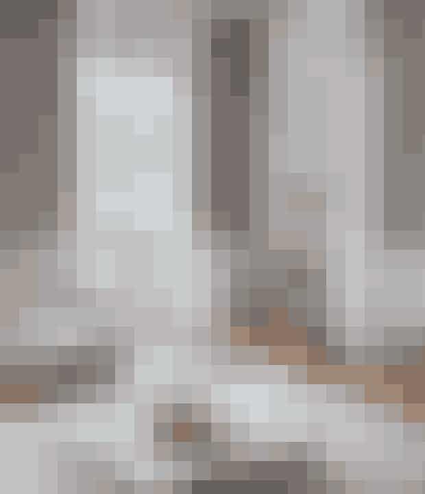 Fremhæv de sprøde hvide nuancer på møbler, paneler og lofter ved at male væggene grå. Sofaen Ghost fås hos CasaShop, lignende flagermusstol kan fås hos Casanova Møbler, gulvtæpperne er fra Zara Home, og skamler og taburetter er rejse- og loppefund. Sofabordet er fra Fly, og messingbakken er fra Caravane.