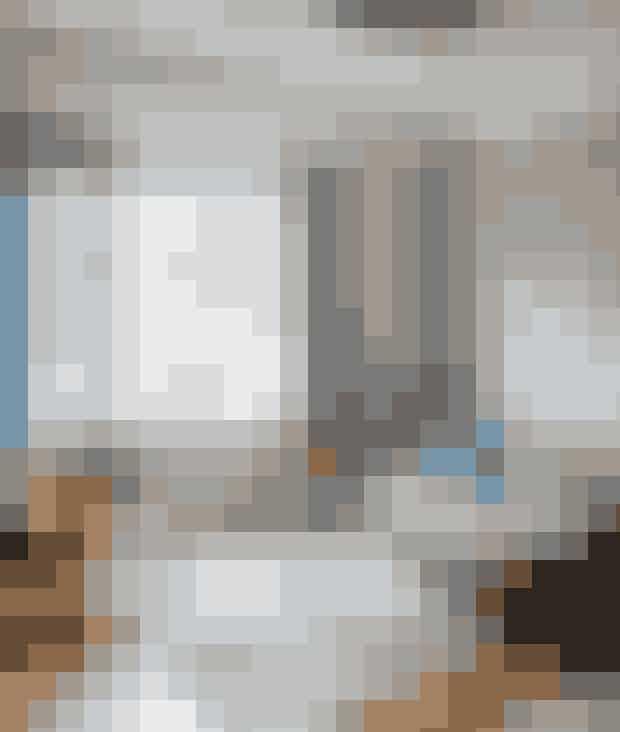 I stuen hersker rolige nuancer af grå, kun stolen og det lille sidebord af teaktræ byder ind med varme toner, mens hyacinter, levende lys og de spinkle kranse i vinduet sørger for julehyggen. Sidebordet er et loppefund, og Wegners Skalstol CH07 er fra Carl Hansen & Søn. Gardinet er fra Designers Guild, Sofaen er fra Ilva, og det marokkanske tæppe er fra Seasons by Sidsel Z.