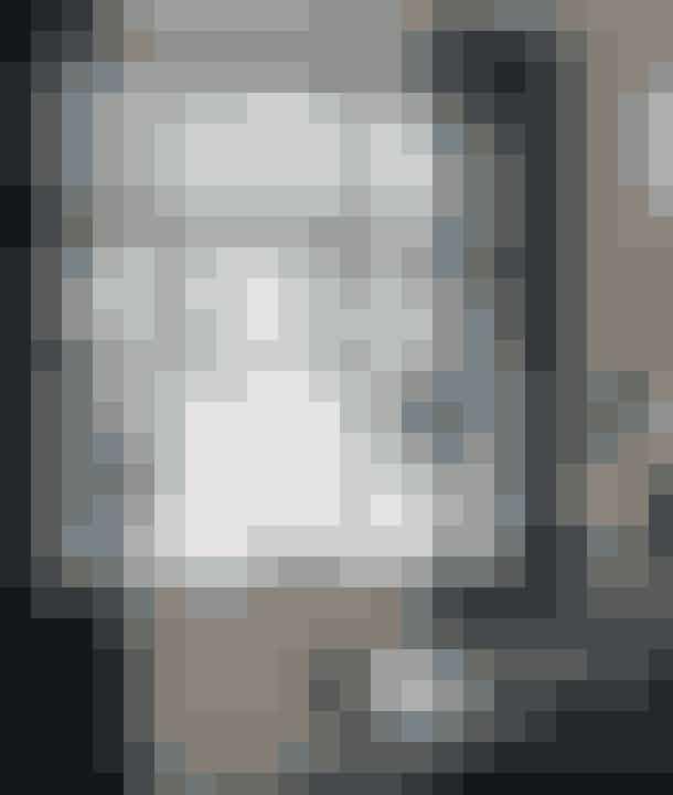 Hvide juleblomster og lærkegrene er sat i vaser, og i vinduet hænger et par diskrete stjerner og en fin grankrans – let og elegant. De mørke transparente gardiner spiller sammen med farven på spisestuemøblerne. Gardinerne er fra Designers Guild. Glaslampen i vindueskarmen er fra Boho Habits, og lysestagen ved siden af er fra Kähler. Vasen er fra Ditte Fischer.