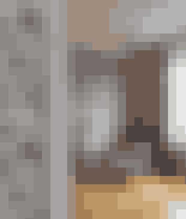 Tapetmix behøver ikke at virke uroligt. Man skal bare huske at vælge tapeter i samme farvenuancer. Her er sat tapet med bladmønster på den ene væg, og på den anden hænger et tapet med grå felter. Farven grå går igen i gardinet og på lænestolen med puf fra Hay. Begge tapeter er fra Designers Guild. Serveringsvognen er fra Normann Copenhagen.