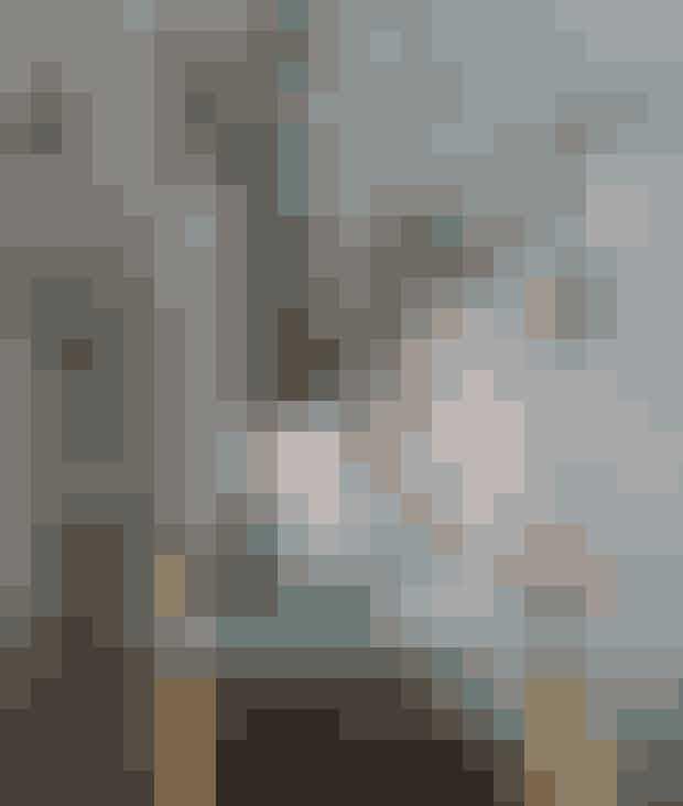 Et bakkebord i træ og mintgrøn bryder de grå flader. Pernille Mikkelsen har sat grafiske grene i en vase og hængt enkel grå og sort pynt på dem. Lysestagen med hjort og grantræ er fra Finnsdottir, mens brevpressen af glas er fra Seasons by Sidsel Z. Bordet og vasen er fra Normann Copenhagen.
