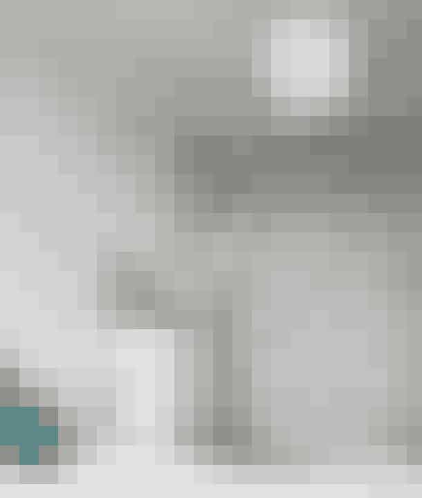 Et tapet med nostalgisk motiv giver en romantisk stemning i soveværelset. Sarte grønne nuancer på velourpuden og loppemarkedsskamlen med skindsæde skaber ro. Væglampen Caravaggio er designet af Cecilie Manz og er fra Lightyears. Metalhylden er fra Anne Linde. Kommoden er fra Ikea. Tapet og pude er fra Tapet-Café.