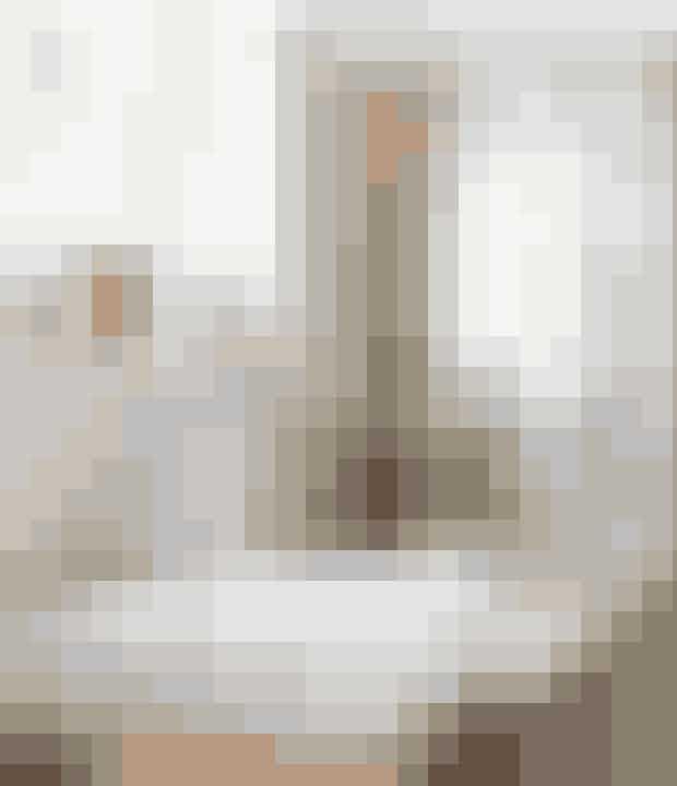 På badeværelset går det mørke træ igensom i resten af boligen. Armaturet er fraVola, og spejlet fra et loppemarked.