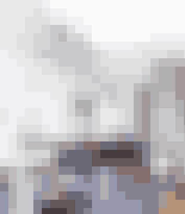 Køkkenet står stadig,som da parret overtog huset – de har blot sat hvidemarmorfliser fra Mosaikhjørnet op på væggen og revetoverskabe ned. På hylden fra Ferm Living (Find den her!) står et billede fra Alexander McQueen-udstilling påQ&A i London. Planten er fra Ikea.