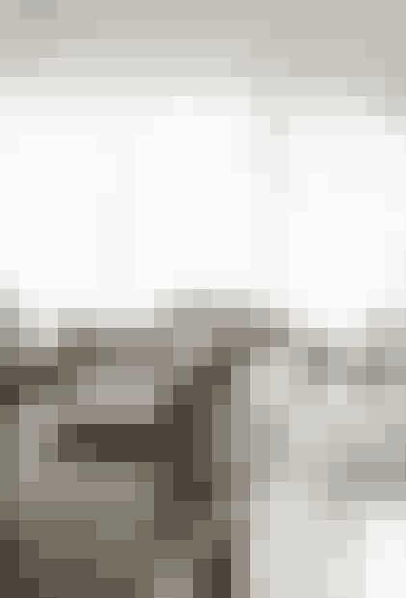 Et glasparti på fem meter og florlette gardiner adskiller stuen fra terrassen. Møblerne er holdt i lyse naturfarver eller træ, og der er ingen tæpper på gulvet, hvor betonen går igennem hele boligen og ud på terrassen. Sofaen er fra Borgo delle tovaglie, og det hvide sofabord er fra Artemide, designet af arkitekten Vico Magistretti ca. 1970.