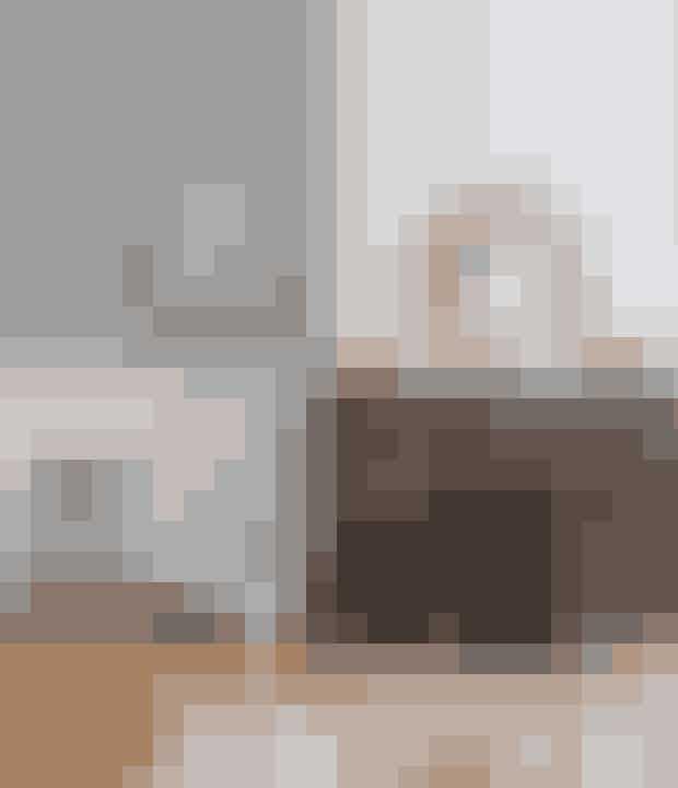 Omkring den gamle pejs af marmor og messing står skamler og lamper i et helt simpelt design for at skabe en kontrast til den elegante stil. Gulvlampen er fra Light by Nath. Det runde spejl af rattan over pejsen er et genbrugsfund. Wiingaard Boheme Interieur har lignende gamle glaskupler. På gulvet ligger en diskokugle. De fås bl.a. hos Disconetto.dk.