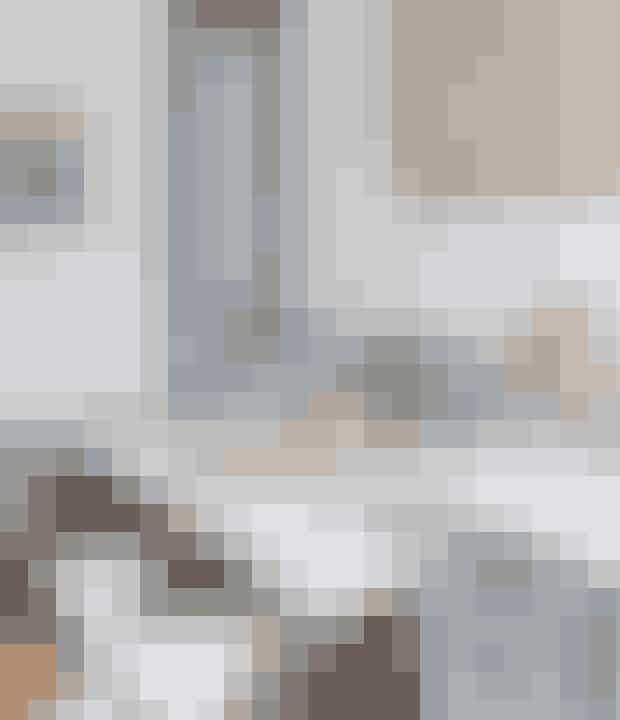 Naturflet på væggen og plastikskamler på gulvet – vælger du en neutral farveskala, kan du mixe de mest usandsynlige materialer og få et harmonisk resultat som her i spisekrogen i køkkenet. Bordlampen er et loppefund, Tam Tam-taburetterne fås fx hos Connox.dk, og bordet er et genbrugsfund.